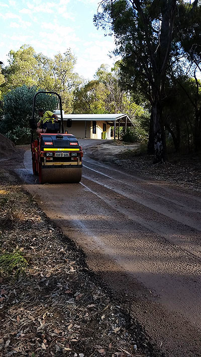 Rolling recycled roadbase for compaction of a driveway